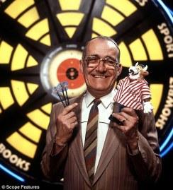 """""""Bullseye"""" host Jim Bowen in front of the famous dartboard."""