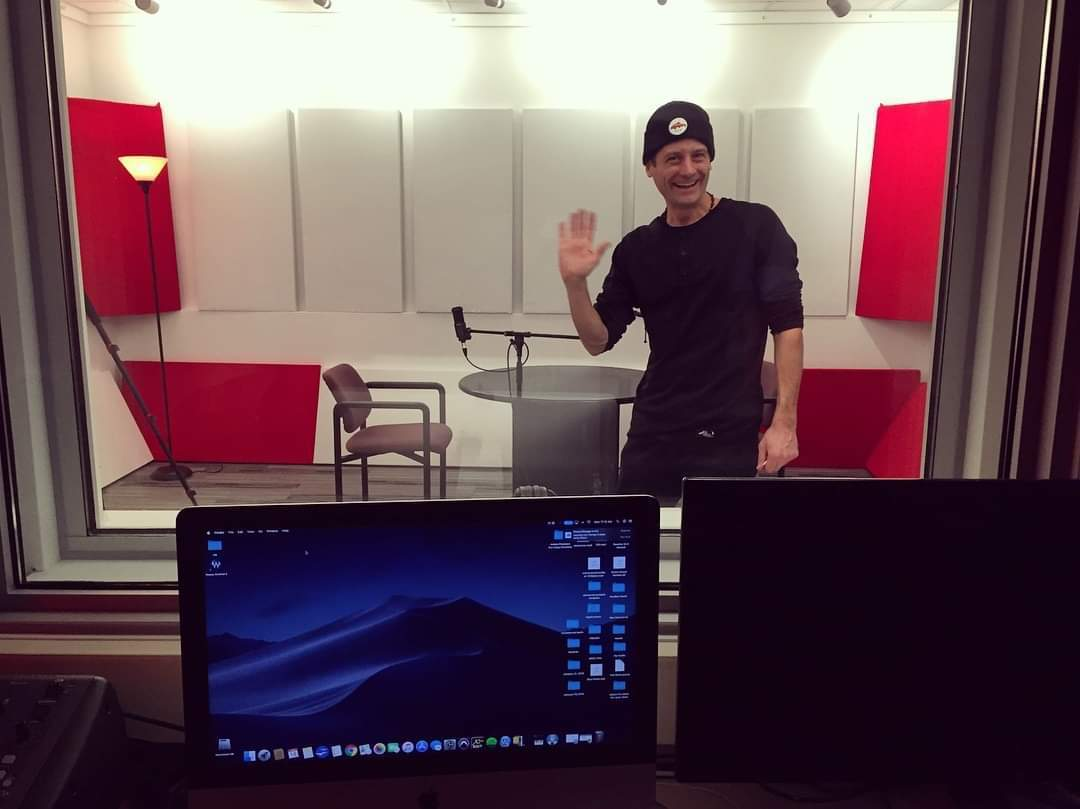 Richard from RFPMedia waving hello from behind the soundproof glass in their professional sound studio at 176 lakeshore Drive