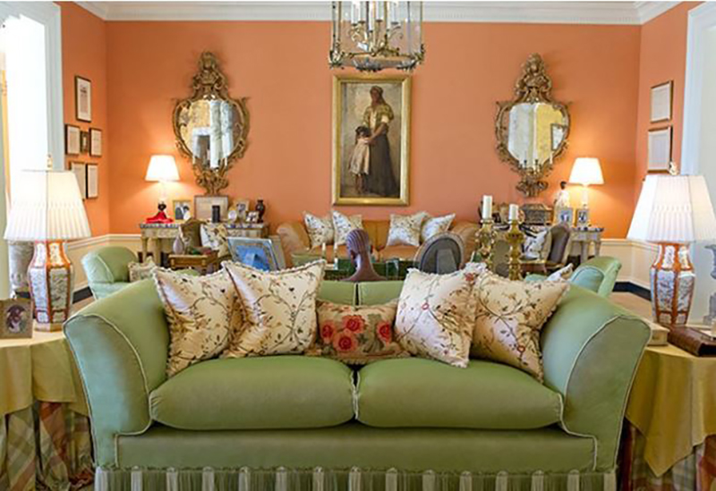 One of Oprah's living rooms has coral-colored walls and green couches.