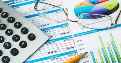 Picture of accounting chart on paper with glasses and a calculator