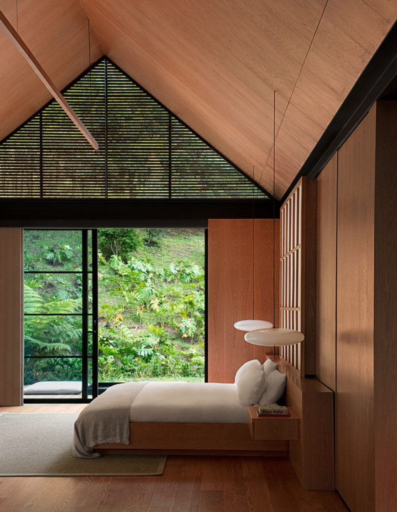 Wood paneled bedroom with large windows to see the outdoors. Also includes white, plain bed linen for a calm, peaceful vibe.