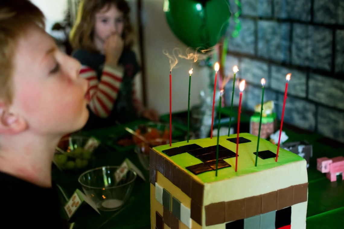 Blowing out candles on Minecraft cake