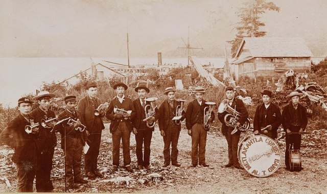 Members of the Metlakahtla Cornet band, a group of Native American brass musicians, pose for a picture next to buildings by the shore in an Alaska town, ca. 1892.