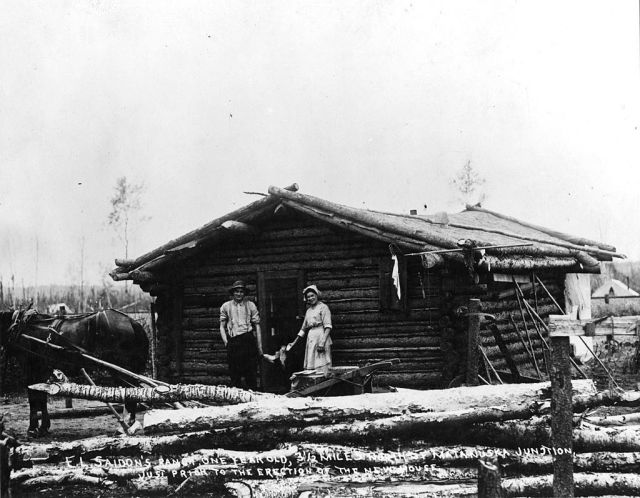 Man and woman as they pose at the doorway of a log cabin, Alaska, 1860s