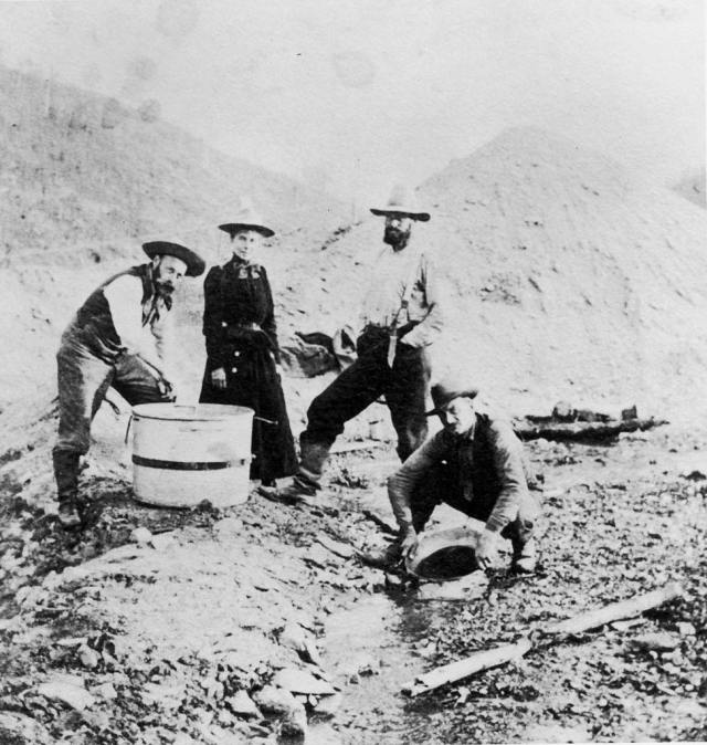 Three men and a woman standing and crouching around a riverbed while panning for gold during the Klondike gold rush, Alaska, 1895.
