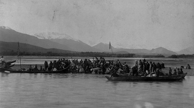 Tlingits gather on bank of a gravely sandspit for a potlatch dance, prior to the actual potlatch feast, along the Chilkat River. Alaska 1895.