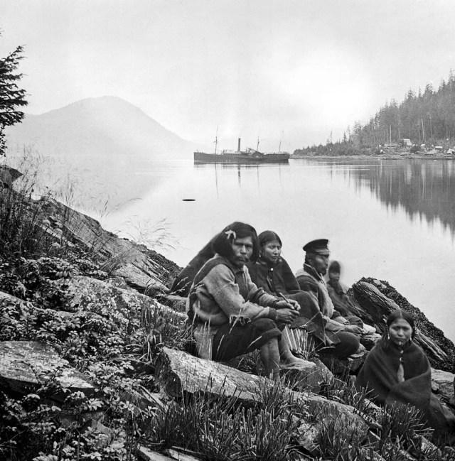 Amerindian family sitting beside a waterway, Alaska, 1868.