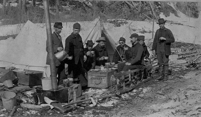 A group of prospectors eat lunch on a crate, on the Yukon Trail. Alaska, 1897.
