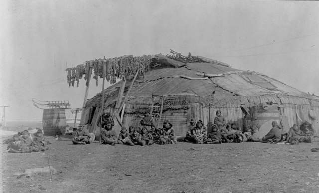 A group of Eskimos sit out side a large round house build out of wood and animal skins. Walrus meat dries on poles next to entrance, St. Lawerence Island, Alaska, 1897.