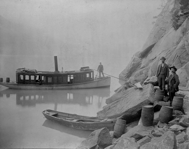 Two customs officals seize untaxed alcohol in Skagway, Alaska 1897.
