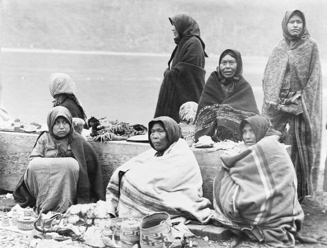 Tlingit women selling baskets and other small items, at the Treadwell Mine site, for tourists arriving in Alaska by steamship, January 1890.