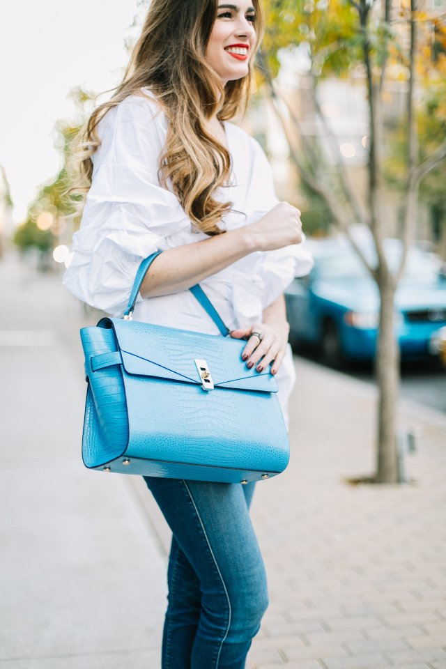 Hilary Rose wearing a blue Henri Bendel bag with a chic wish wrap top in downtown Austin | By, Hilary Rose