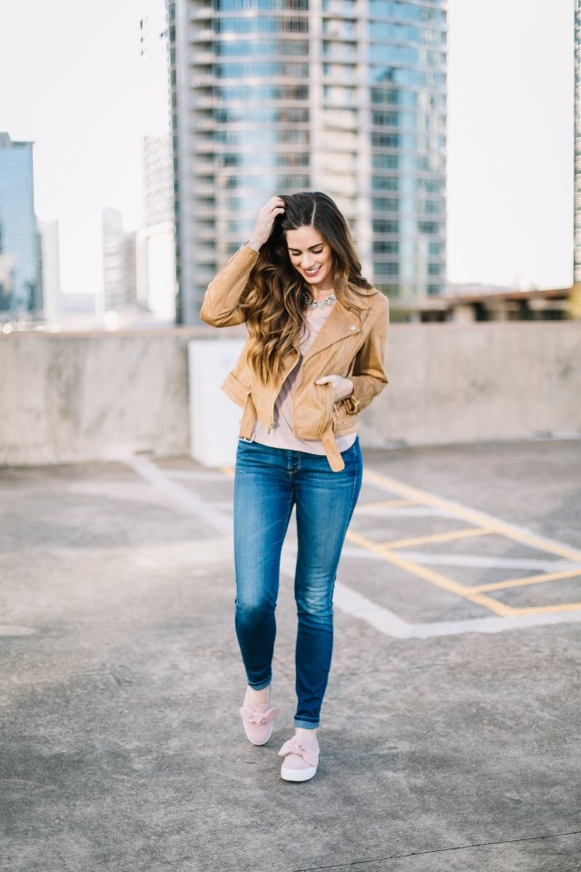 By, Hilary Rose wearing a faux suede moto jacket with Rebecca Minkoff slide on sneakers and a baublebar necklace in downtown Austin, TX