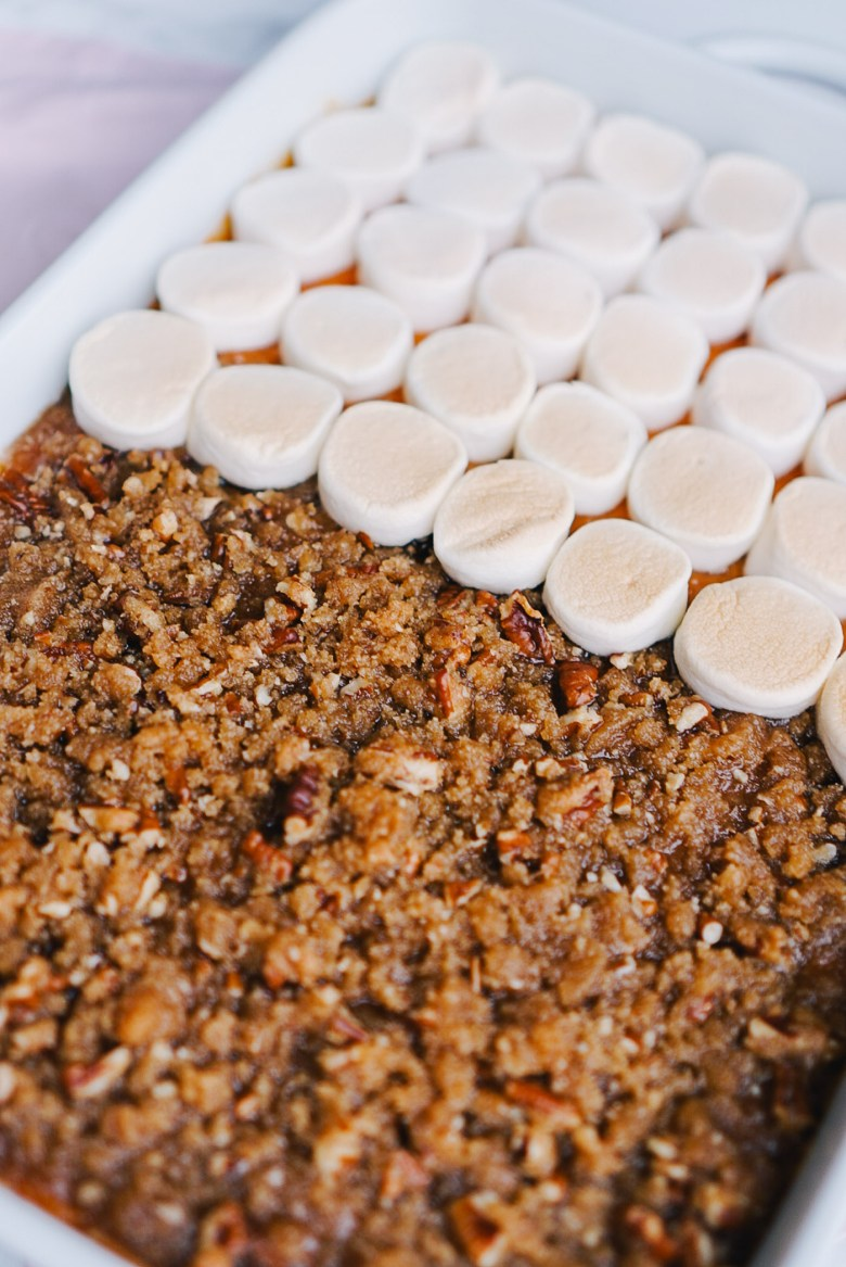 Sweet potato casserole with half crumble topping and half marshmallow topping in white baking dish