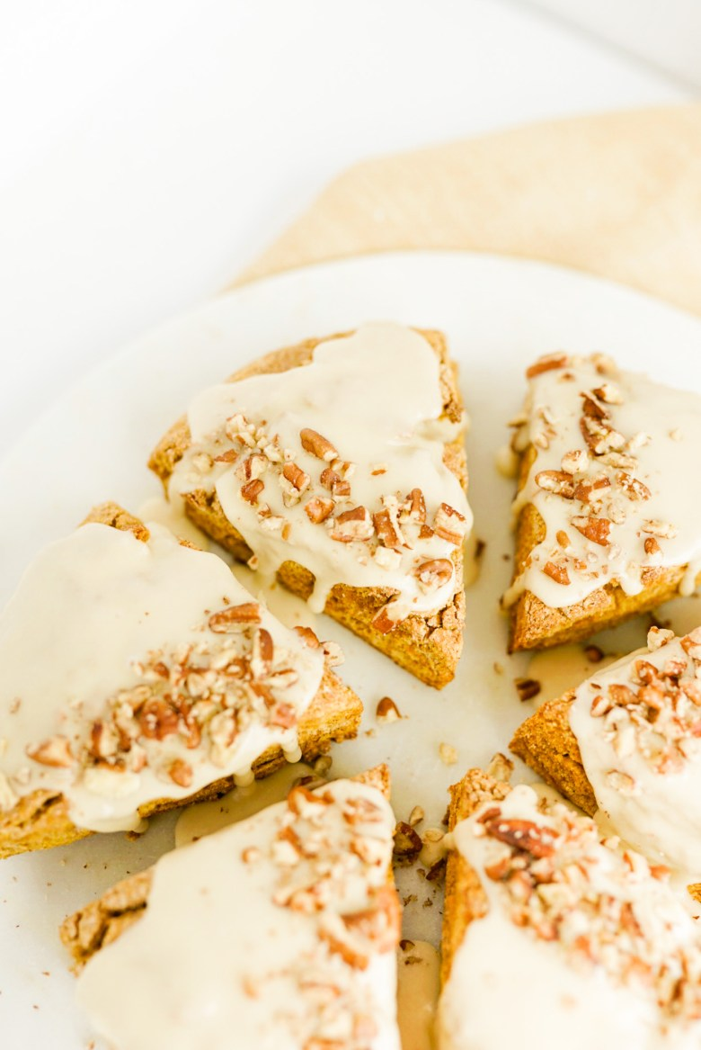 pumpkin scones with glaze and crushed pecans on white marble pastry board