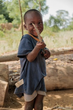 boy with a shy smile and machette