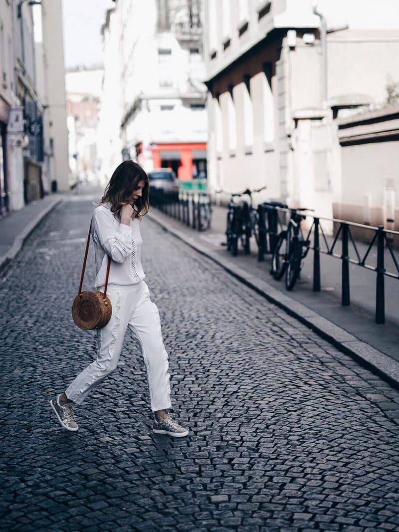 Look pantalon blanc à volants, blouse Navy Paris, sac rond Bali et baskets à paillettes marche