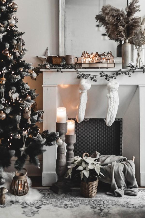 Décoration de Noël nature avec cheminée en bois blanc. Les chaussettes blanches en tricot sont suspendues.