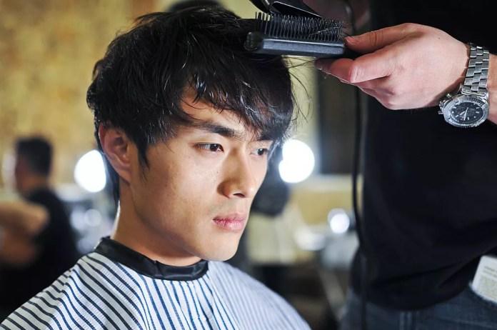 Asian man getting a hair cut