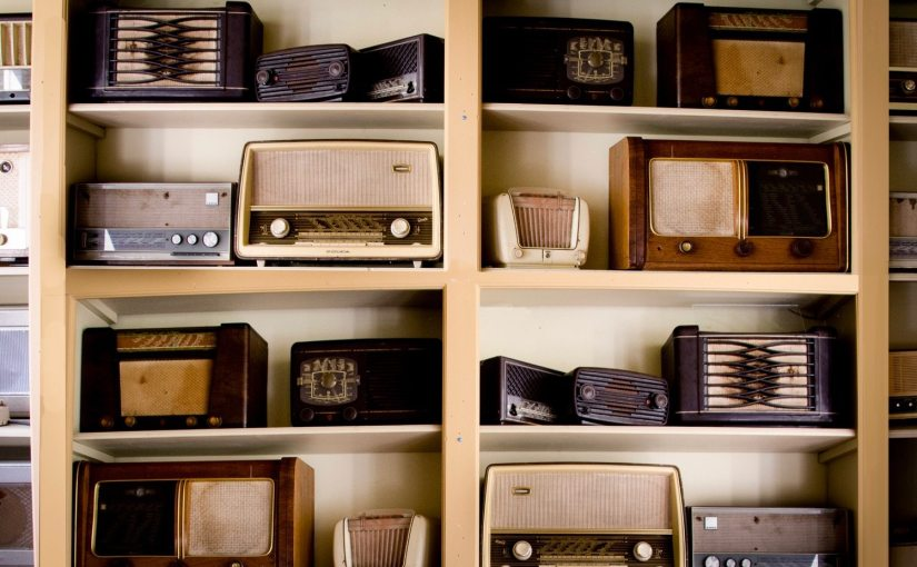 Picture of vintage radios on shelves.