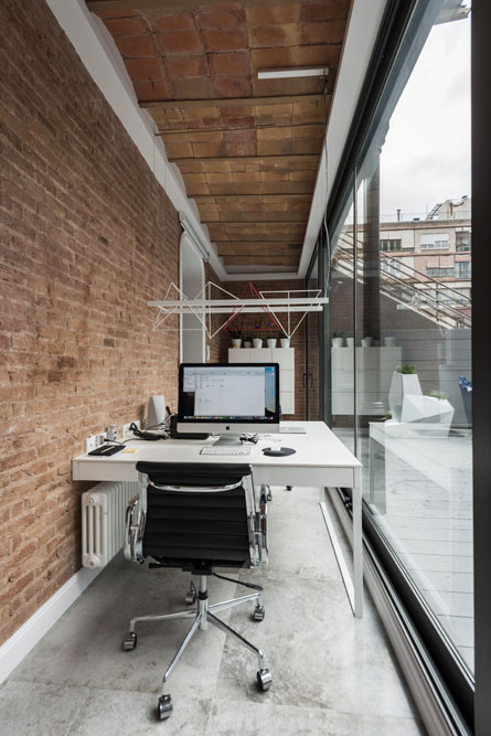 Despacho en porche patio Eixample con un gran ventanal. Techo con volta catalana.