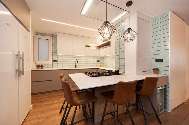 Dos lámparas colgantes de varillas negras en barra de cocina en península