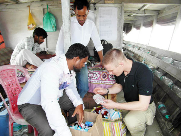 John Hugh Brent Grotrian looking at medical supplies of the Morigaon halth team onboard