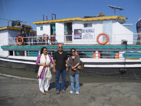 Managing Director, NRL P Padmanabhan with his wife AmbikaPadmanabhan(left) and Communications Officer Bhaswati Goswami with the Boat Clinic SB Numali as backdrop at a river island village in Assam's Sonitpur district
