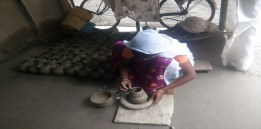While a woman makes clay pots. The village has expert potters.