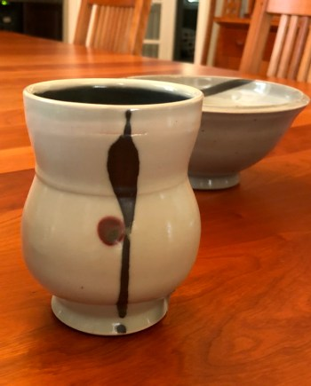 handmade porcelain tumbler on a table with a bowl behind