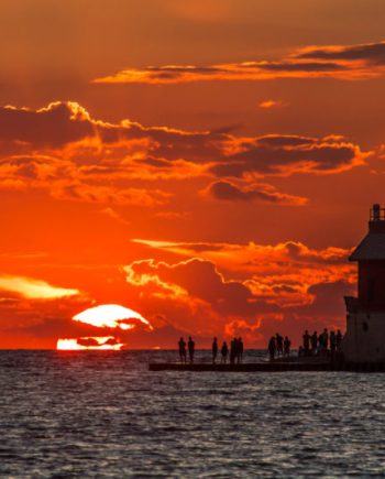 photograph of an orange sky and sun setting in grand haven michigan