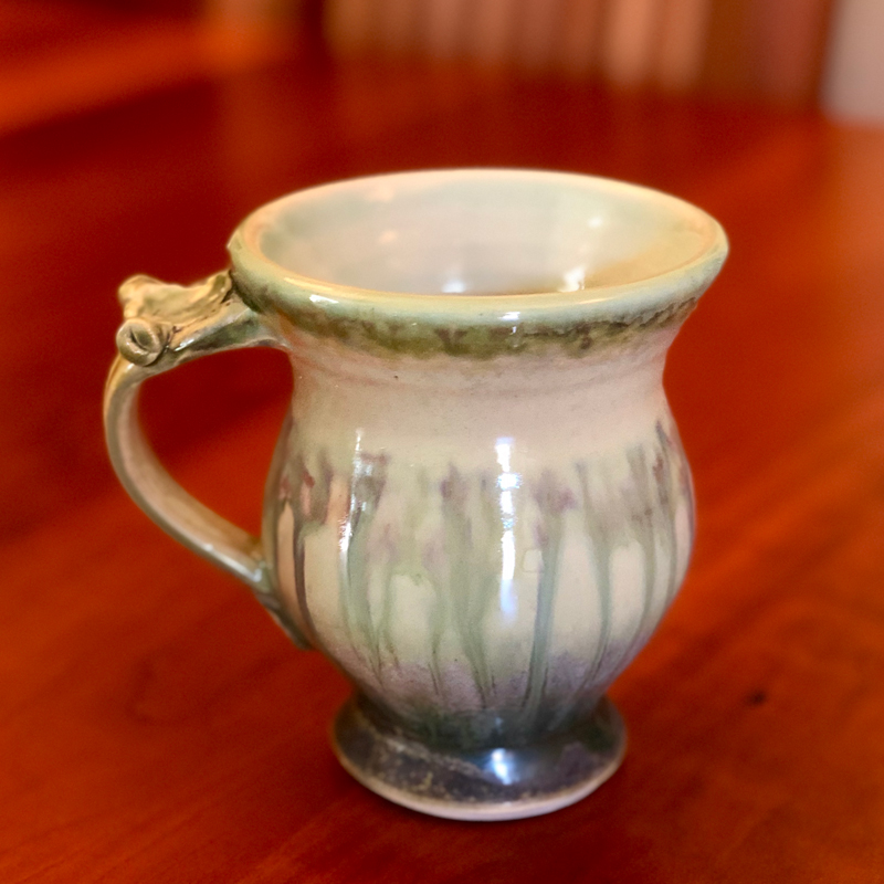 Footed Handmade Ceramic Mug Sitting on a Table