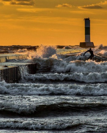 north pier sunset with surfer in grand haven michigan