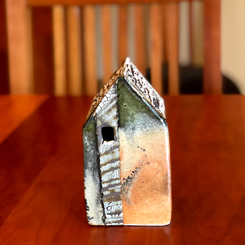 handmade decorative ceramic cottage sitting on a table