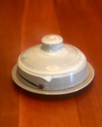 handmade ceramic butter dish with a lid on a table