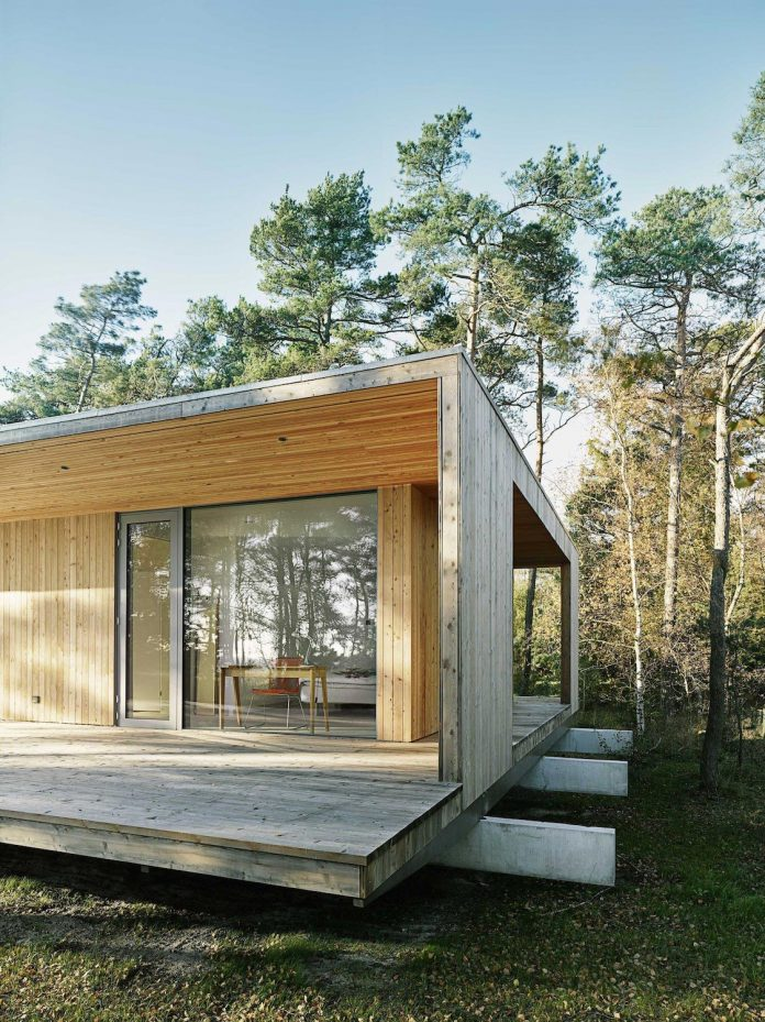 Wood and glass frame of a summer house surrounded by woods on Swedens southern coast