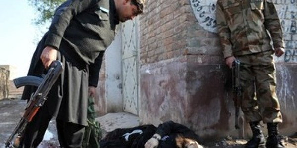 Pakistani security forces look at the dead body an attacker.