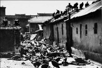 The scene of a massacre (unknown). Vultures can be seen on the rooftops. © BBC.