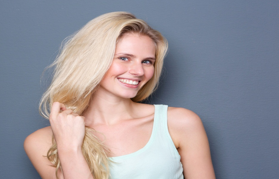 Close up portrait of a beautiful blond hair woman smiling on gray background