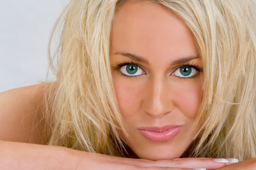 A stunningly beautiful young blond woman with bright blue eyes and a perfect cheeky smile