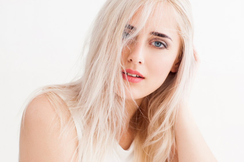 confident blonde with big blue eyes, bright eyebrows. Her long white hair disheveled, she calmly and trustingly and looks into the camera. studio photo on white background.