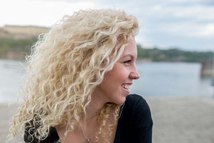 Side view of young woman with curly hair laughing outdoors during a day.