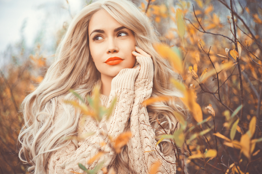 Outdoor fashion photo of young beautiful lady surrounded autumn leaves