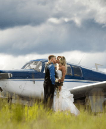 newly wed couple kissing in front of a plane at Cabin Creek Landing B&B wedding services