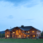 Contact Cabin Creek Landing Bed and Breakfast all wooden lodge in the evening with lights on from our surrounding area
