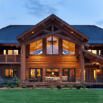 wooden lodge in the evening with lights on