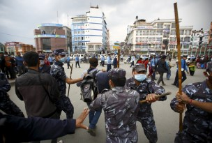 Nepalese police personnel try to stop earthquake victims from blocking traffic along a road as they protest against the government's lack of aid provided to the victims in Kathmandu