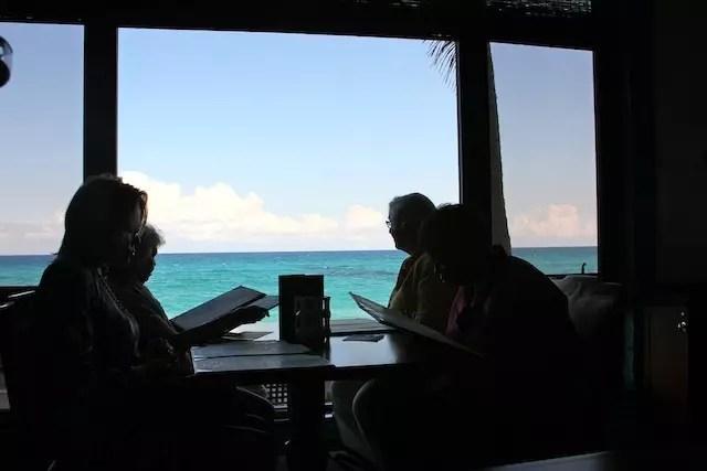 O Seafood bar que tem vista para o mar e um bar com balcão de aquário