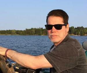 Bob Ohly, Partner and CFO at Caffe Ladro/Ladro Roasting driving a pontoon in Minnesota