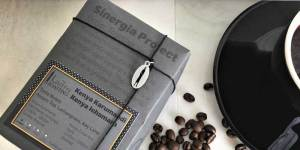 sinergia project from ladro roasting with coffee beans and a black caffe ladro coffee cup and saucer